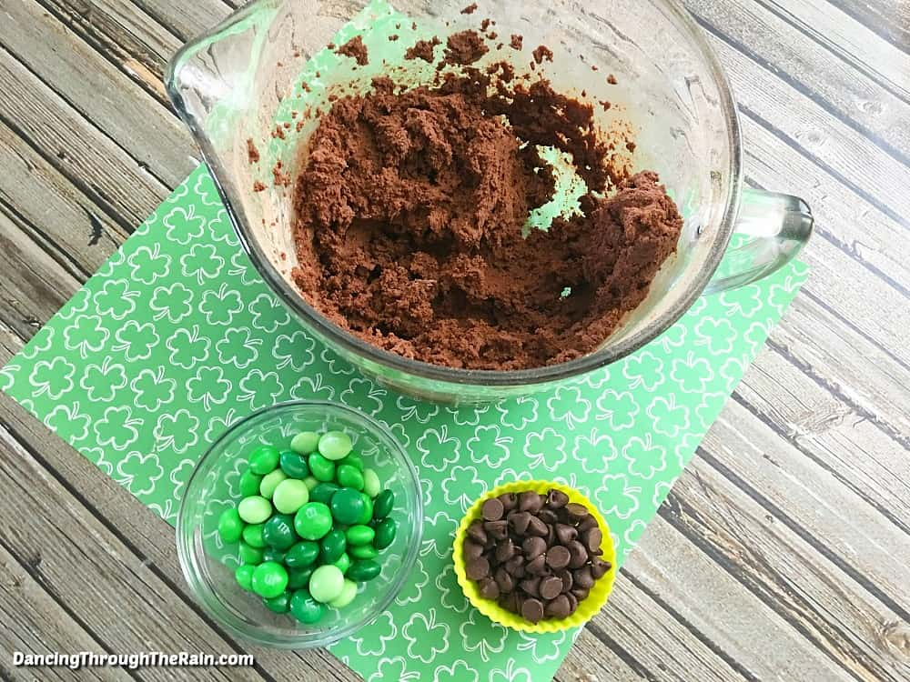Chocolate cookie mix in a bowl next to green M&M's and chocolate chips