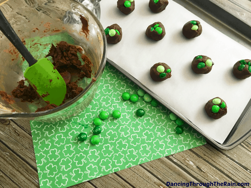 Chocolate cookies with green M&M's on top of a baking sheet