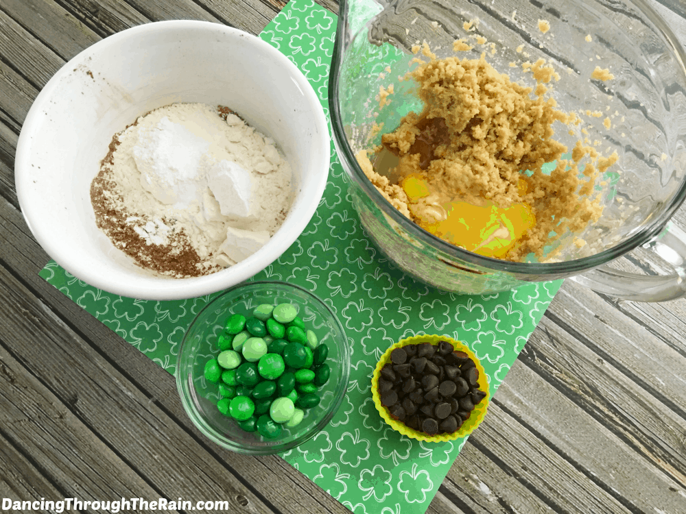 Bowls with green M&M's, chocolate chips, brown sugar with eggs, and flour