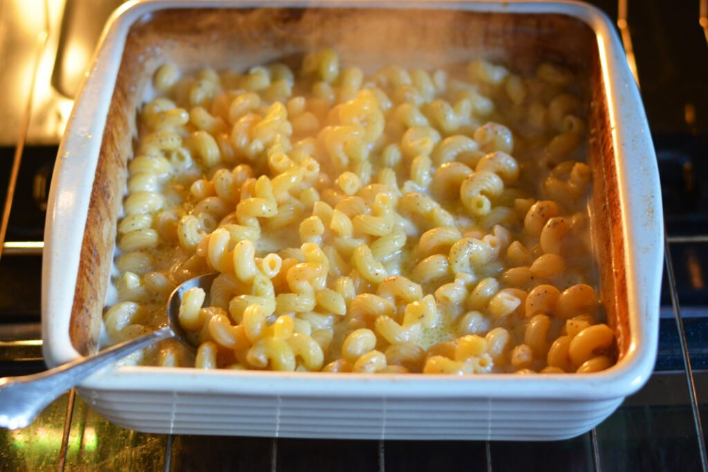 A white baking dish with evaporated milk, pasta and other ingredients being baked in the oven
