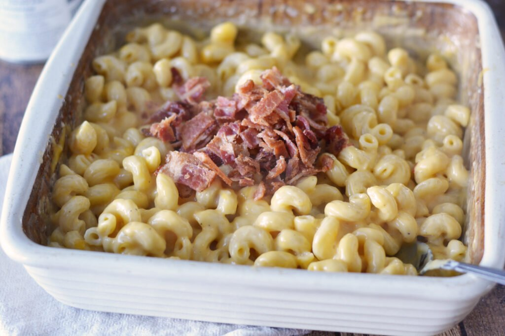 A white baking dish with mac and cheese and a pile of cooked and chopped bacon on top