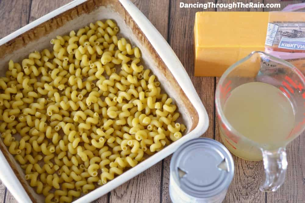 Dry pasta in a baking dish next to cheese and a measuring cup with liquid