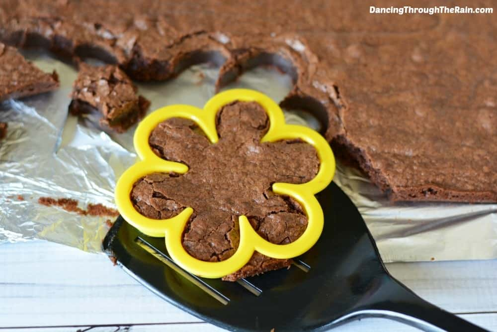 Baked brownies with one on a spatula in the shape of a flower with a flower cookie cutter