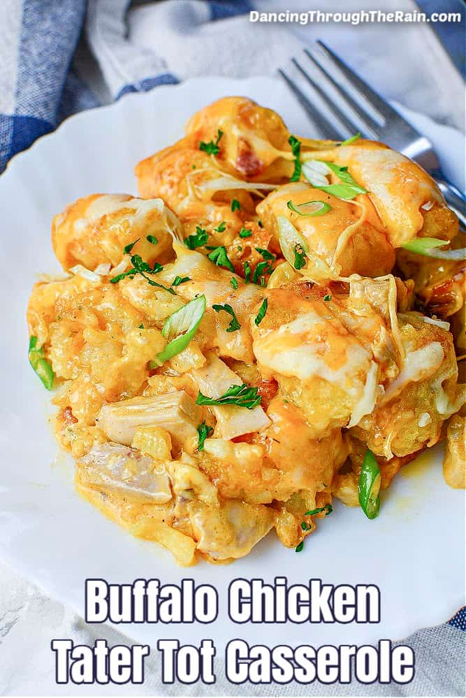 A large portion of Buffalo Chicken Tater Tot Casserole on a white plate next to a metal spoon