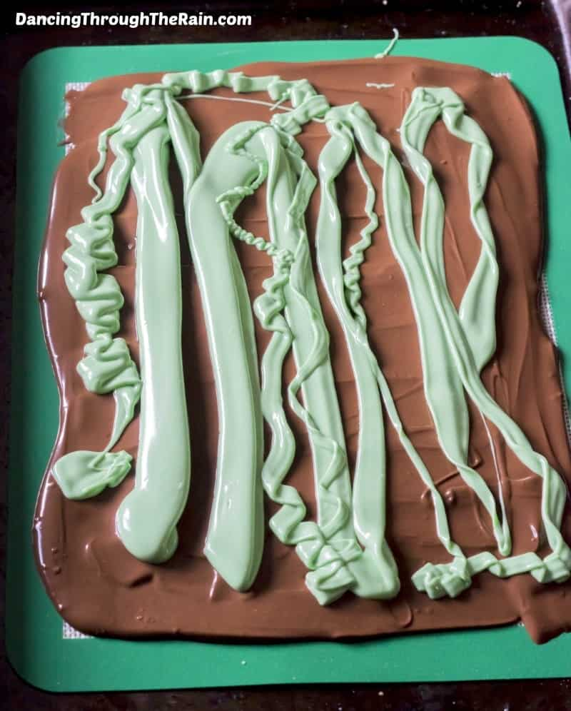 Milk Chocolate with melted green candy melts in stripes on a green board