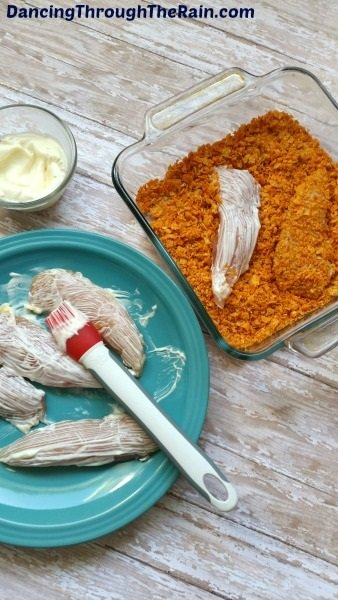 Raw chicken tenders being brushed with mayo next to a dish of Doritos