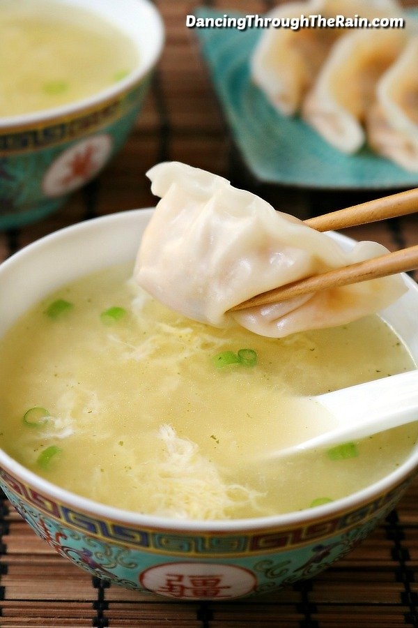 Easy Egg Drop Soup in a white bowl with a white spoon and a pair of brown chopsticks holding a wonton with more wontons and a bowl of soup in the background