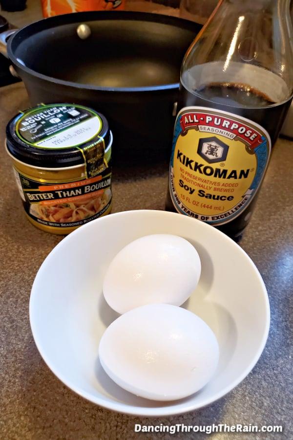 A black saucepan, Kikkoman soy sauce, chicken Better Than Bullion jar, and a white bowl with two eggs on a countertop
