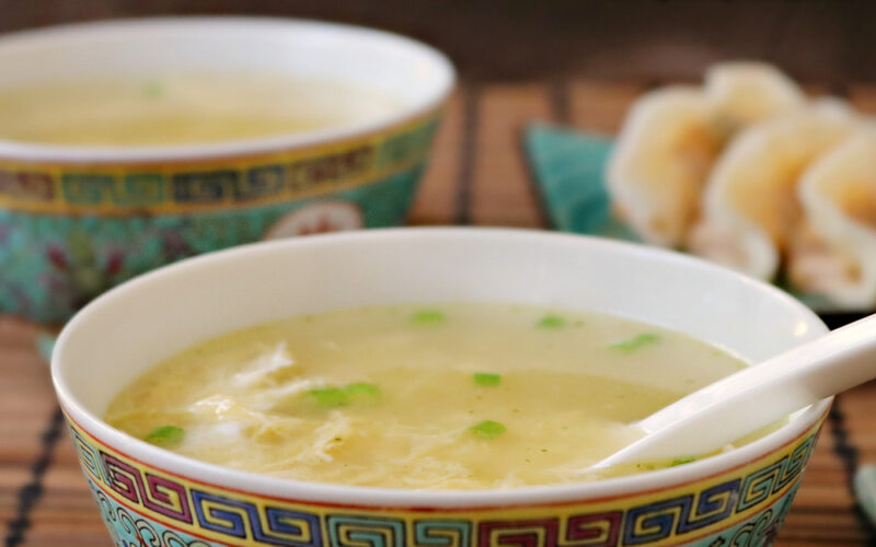 Two bowls of easy egg drop soup on a brown mat with a white spoon inside of one and wontons in the background