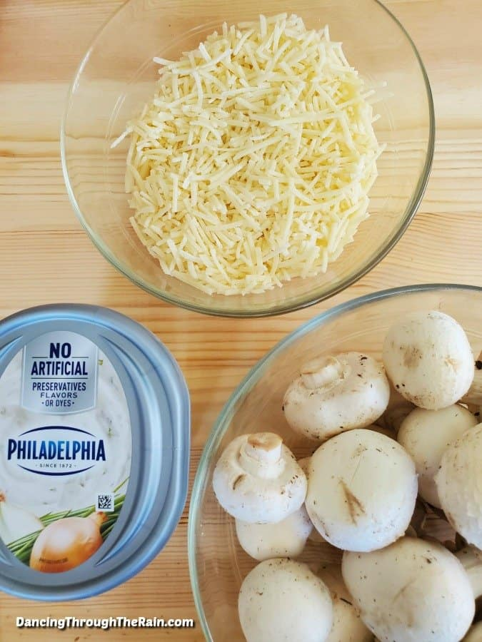 Philadelphia chive cream cheese, a glass bowl of shredded parmesan chees and a glass bowl of whole white mushrooms on a wooden table