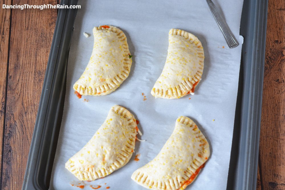 Four raw homemade pizza pockets on a baking sheet lined with parchment paper