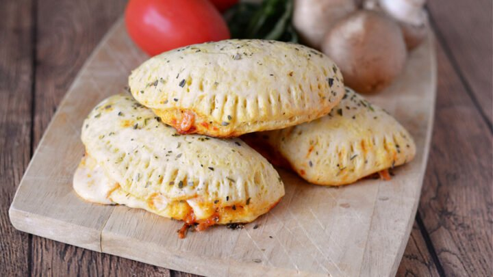 Three easy Homemade Pizza Pockets on a wooden cutting board with whole roma tomatoes, mushrooms and a bunch of spinach
