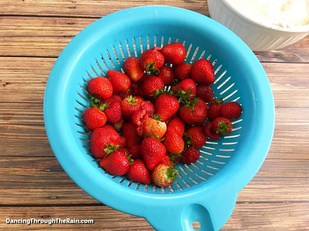 Strawberries in a light blue colander