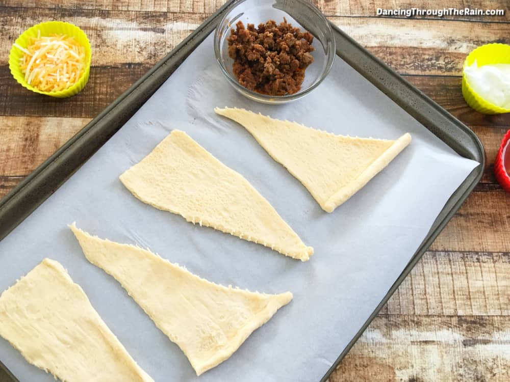 A baking sheet lined with parchment paper and four triangles of crescent roll dough laid out next to a clear bowl of cooked ground beef