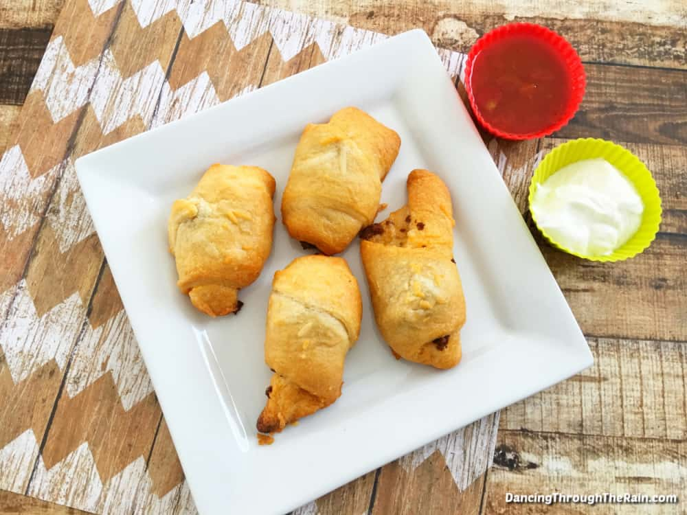 A white square plate with four stuffed taco crescent rolls on it next to a cup of salsa and a cup of sour cream on a wooden table