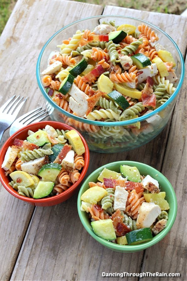 A green and burnt red bowl full of Chicken Bacon Ranch Pasta Salad next to a clear bowl of more on a wooden table