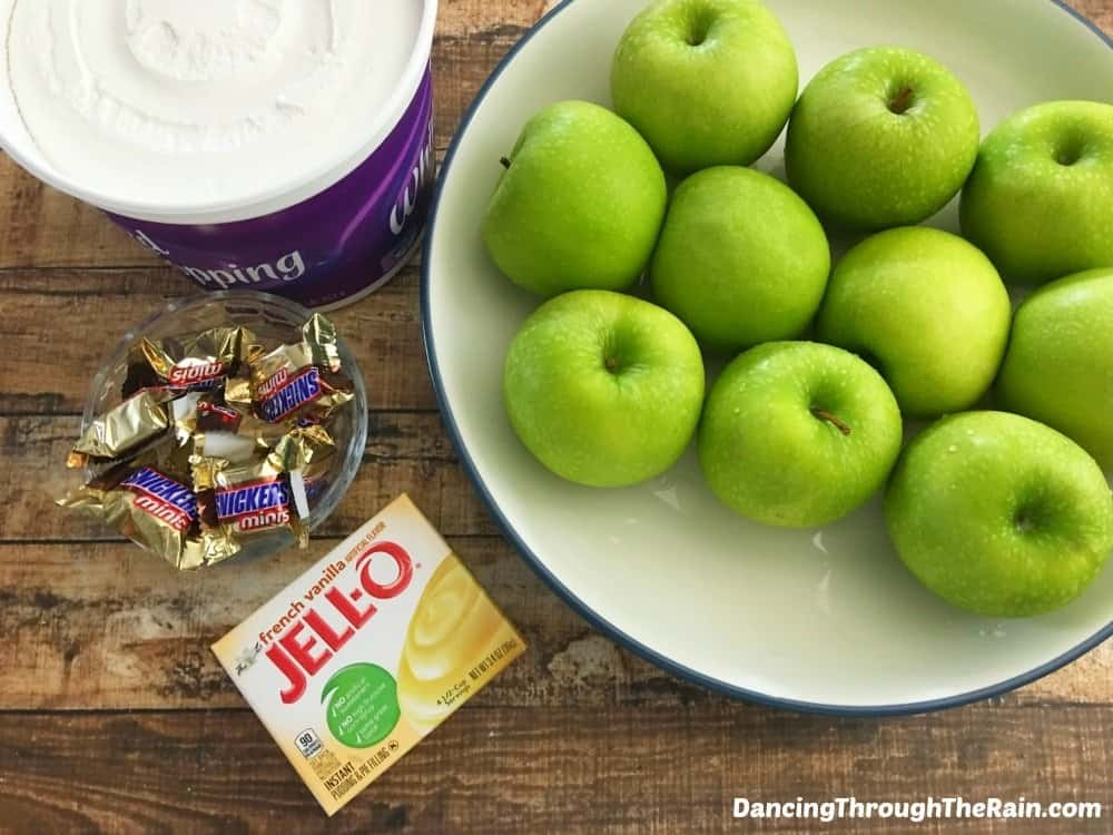 Cool Whip, green apples, Jell-O, and Snickers on a table