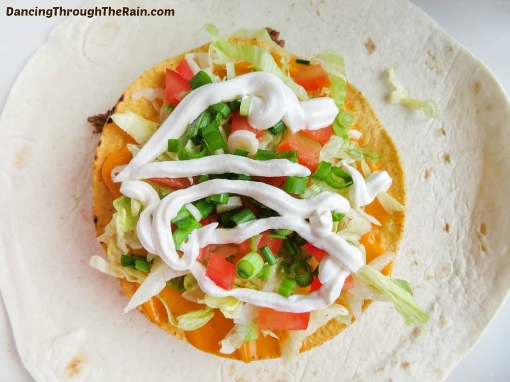 Flat flour tortilla topped with corn tortilla, cheese, lettuce, tomatoes, sour cream and onions