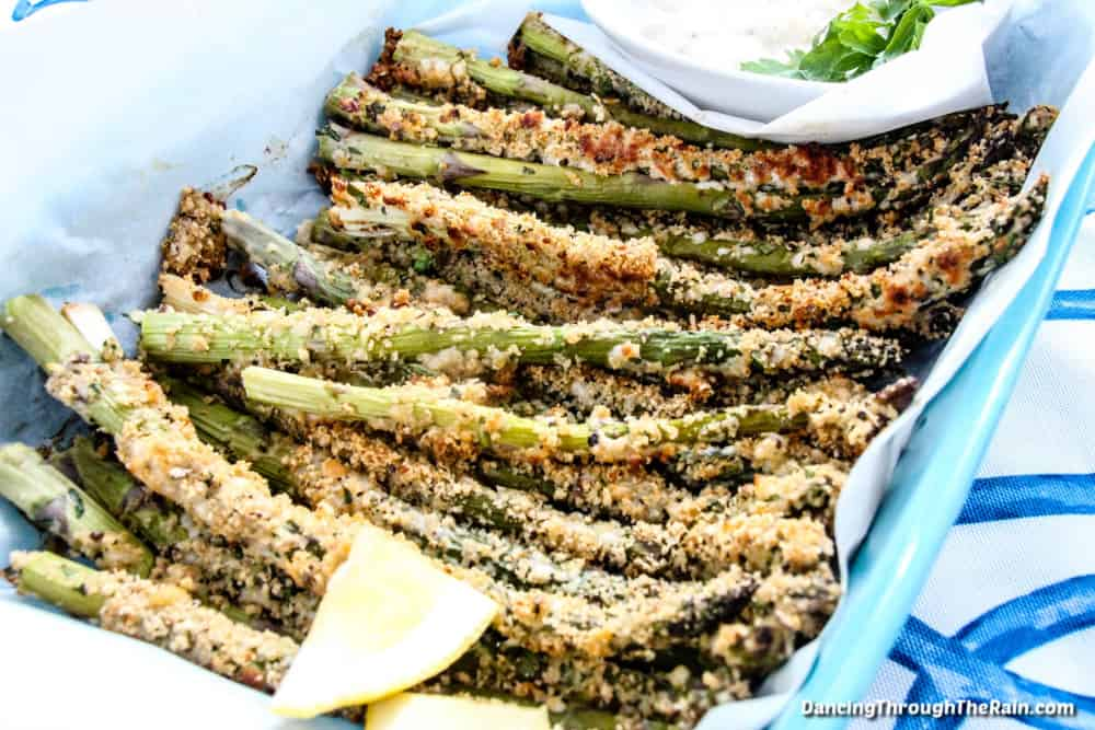 A single layer of Crispy Baked Parmesan Asparagus Fries on a white plate next to a lemon wedge