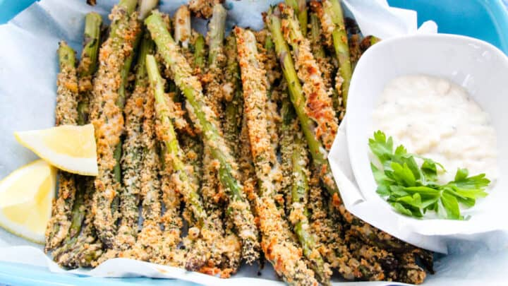 A bunch of crispy asparagus on a tray with parchment paper next to a small bowl of garlic aioli