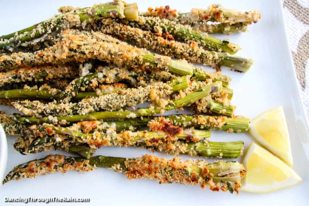 A pile of Crispy Baked Parmesan Asparagus Fries on a white square plate next to two wedges of fresh lemon