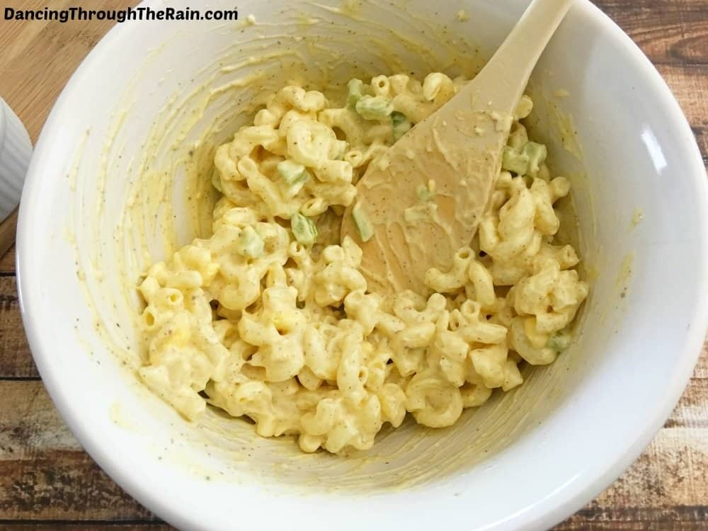 Macaroni Egg Salad ingredients being mixed together in a bowl