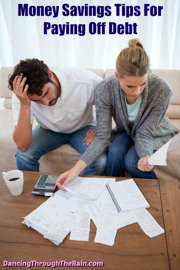 A frustrated man and woman budgeting their bills with a calculator on a table