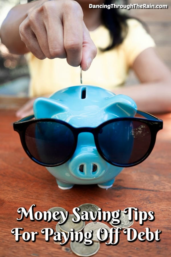 A blue piggy bank wearing sunglasses on a brown table with a woman putting a coin inside