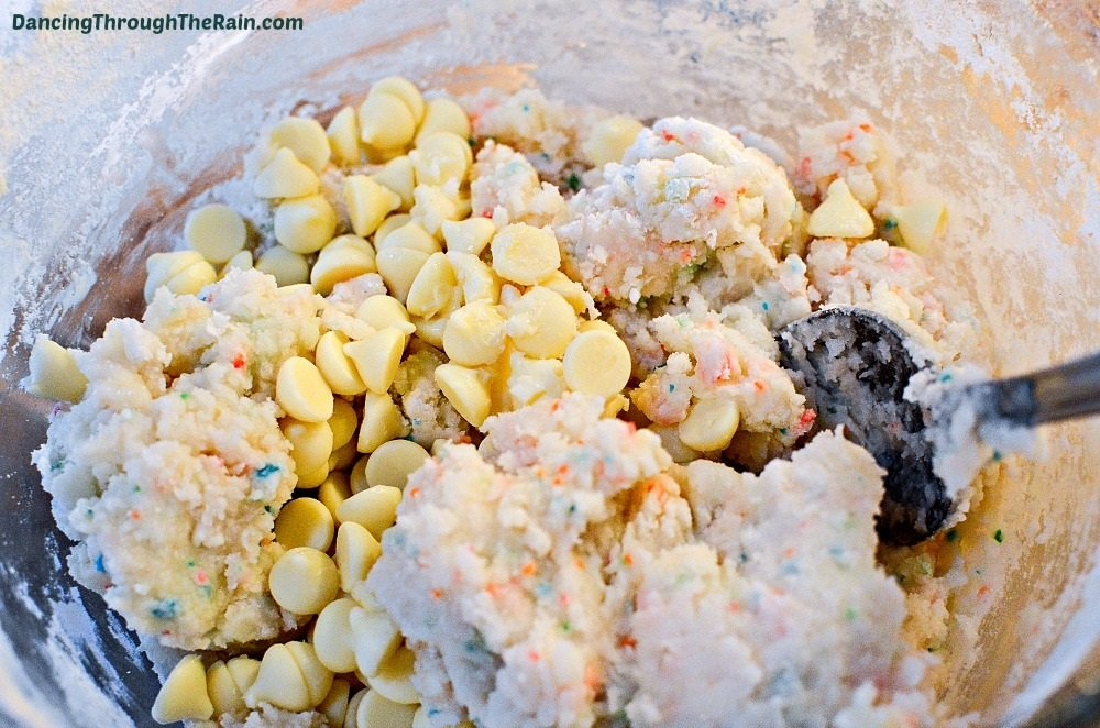 A clear bowl with funfetti cake mix, butter, white chocolate chips, and butter being mixed with a black spatula