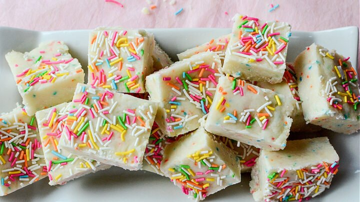A pile of Birthday Cake Fudge on a white rectangular plate on a pink tablecloth