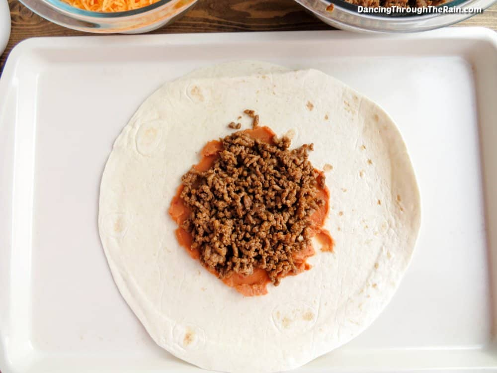 A large flour tortilla with refried beans and ground beef on top next to a clear bowl of ground beef and shredded cheese