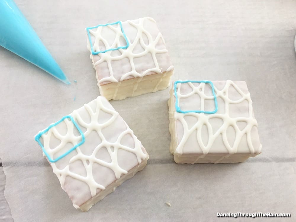 White Little Debbie Snack Cakes with a small blue square of melted candy melts in the top left corner