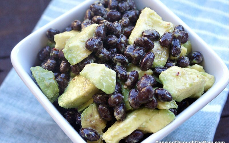 A white square bowl with Black Bean Avocado Salad on a blue tablecloth