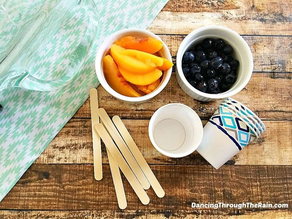 Peaches, blueberries, Dixie cups and popsicle sticks on a table