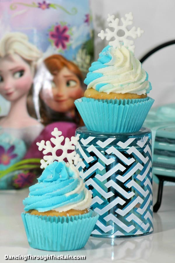 Two Frozen Cupcakes with an Anna and Elsa photo in the background