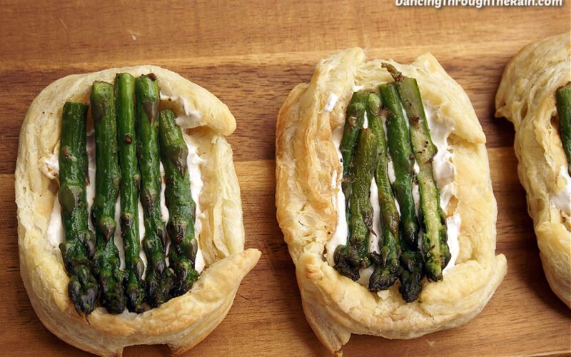 Two Asparagus Puff Pastry Tarts on a cutting board