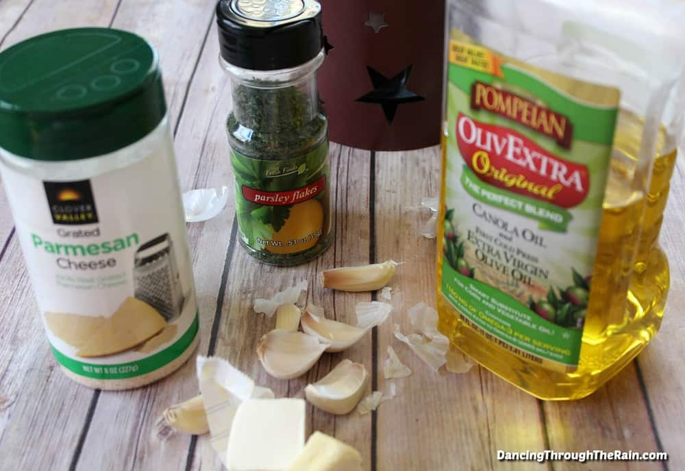 A jar of parmesan cheese, a jar of parsley flakes, olive oil and garlic cloves on a wooden table