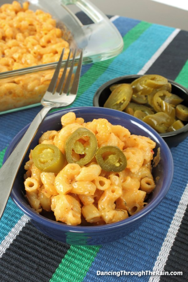 A blue bowl with spicy mac and cheese inside next to a bowl of jalapeno peppers and the pyrex baking dish with the rest of the casserole