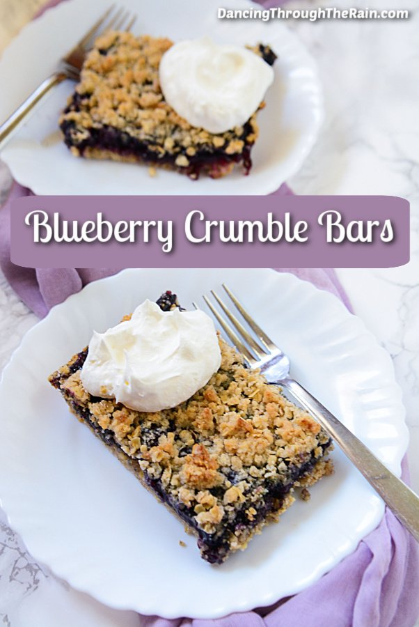 One of the Blueberry Crumble Bars on a white plate with a metal fork in front of another bar on a plate with a purple tablecloth underneath