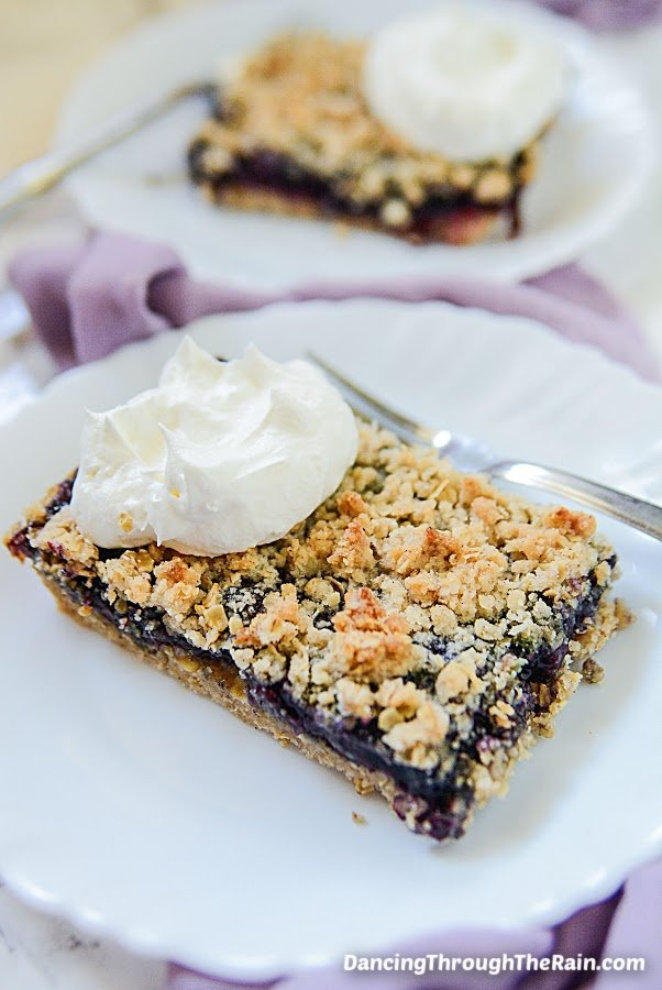 Two plates with Blueberry Crumble Bars and a metal fork on a purple tablecloth