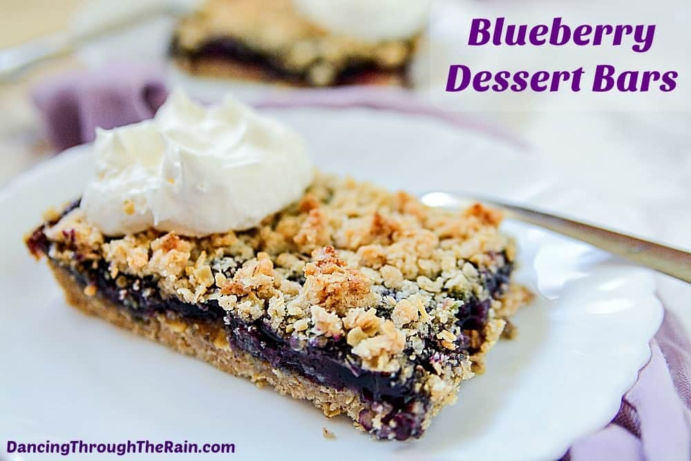Blueberry Dessert Bars with whipped cream on white plates