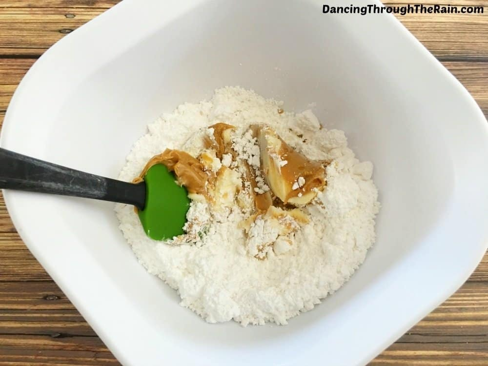 A white bowl with powdered sugar, peanut butter and butter being stirred together with a green spatula