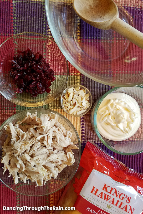 Clear bowls of shredded chicken, dried cranberries, mayonnaise, slivered almonds, and a package of King's Hawaiian buns