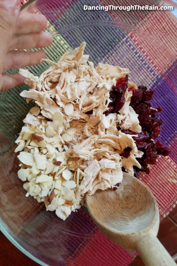 Shredded chicken and dried cranberries in a clear bowl with a wooden spoon