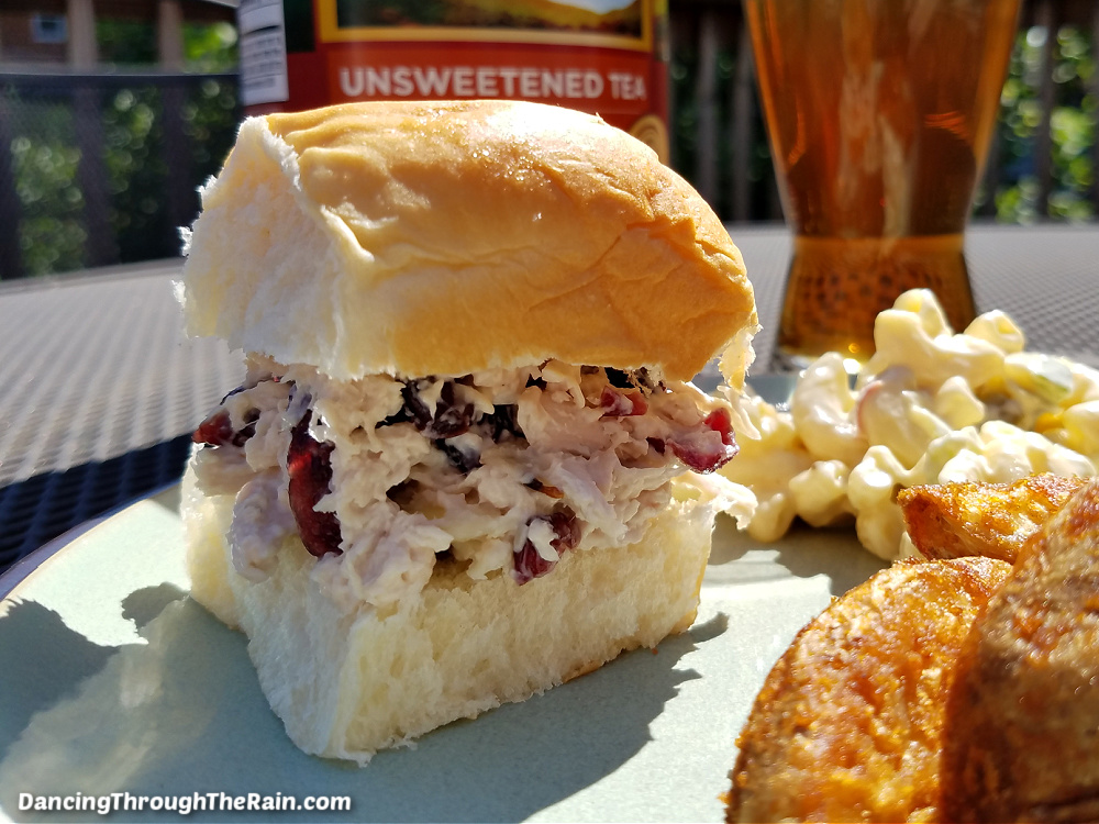 Easy Cranberry Chicken Salad on a bun next to potato wedges and macaroni salad