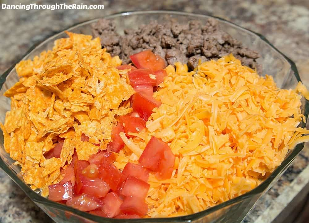 A clear bowl with diced tomatoes, shredded cheddar cheese, crushed Dorito chips, and ground taco meat in a clear bowl