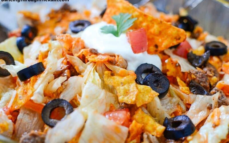 A closeup of Dorito Taco Salad with Doritos chips, olive slices, iceberg lettuce, tomatoes, and sour cream visible