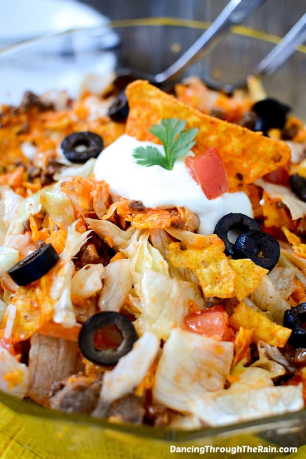 Dorito Taco Salad in a clear bowl with two metal utensils inside on a wooden table