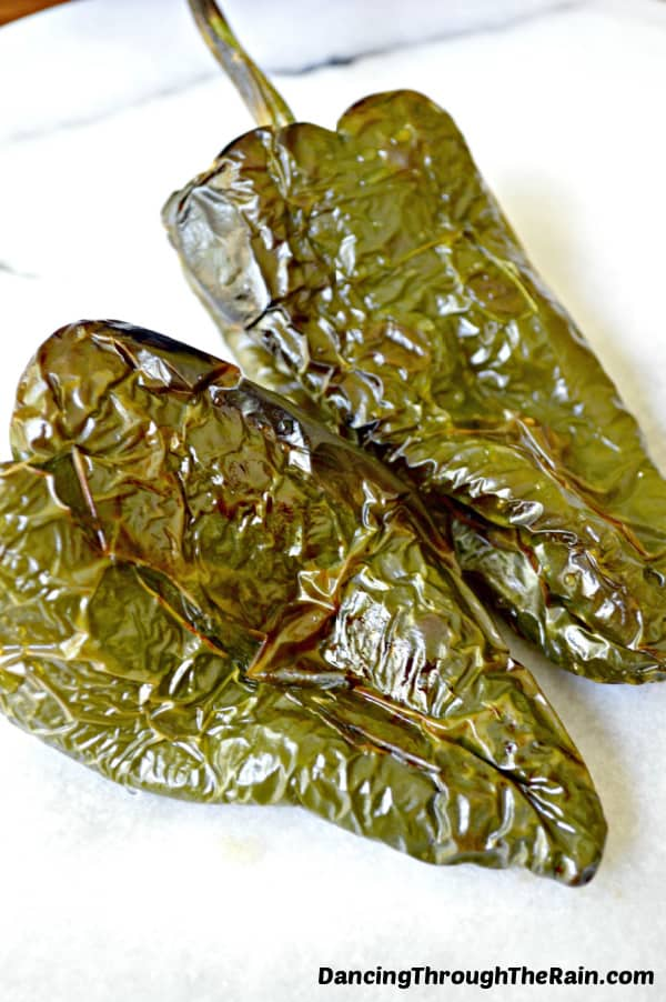 Two roasted poblano peppers on a white table