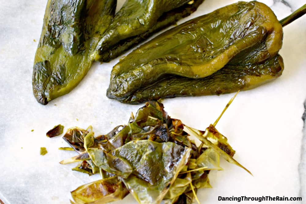 Two poblano peppers with the skins being scraped off on a white cutting board